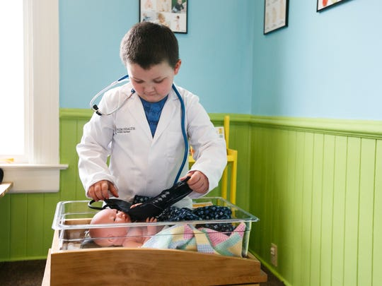 """Carson Wetzle, 5, plays doctor with a baby doll and a lab coat at a new exhibit at the Gilbert House Children's Museum. The """"All About Me"""" exhibit has a microscope station, diagnostic imaging of body parts, a baby nursery and other equipment to teach children about the health and medical professions."""