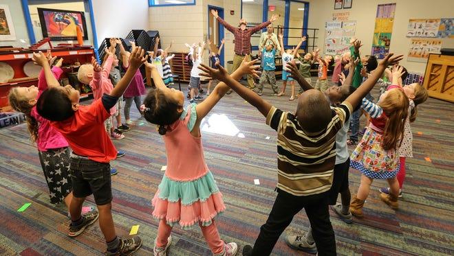 Lowe Elementary music teacher Josh Gumm works with Kindergarten students from Tymna Oberhausen's class.