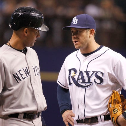 Yankees shortstop Derek Jeter, left,.  talks with  Rays third baseman Evan Longoria  during the sixth inning at Tropicana Field.