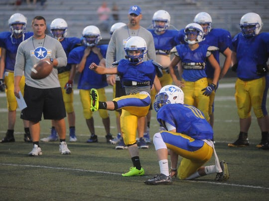The Mountain Home Bombers run through the placekicking portion of their practice Friday night at BomberFest.