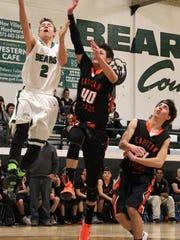 Cloudcroft's Tyson Hughes, left, attempts a layup while being guarded by Capitan's Enrique Hernandez, 40, Tuesday night.