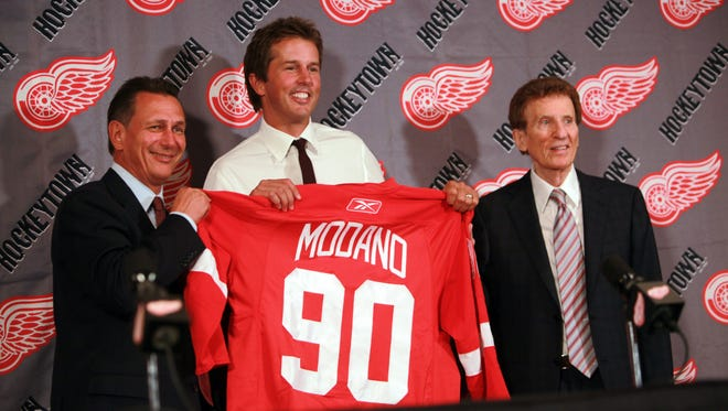 Red Wings GM Ken Holland, Mike Modano and Red Wings owner Mike Ilitch hold up Modano's jersey on Aug. 6, 2010.