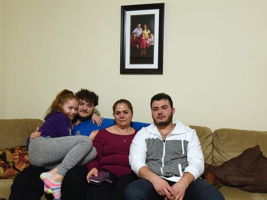 Neta Pukri sits beneath a family photo with her children, from left, Angela, age 10, Mikel, 21, and Bepin, 26. She must wear an ankle monitor, and her husband, Vitor, is being held at the Elizabeth Contract Detention Facility.