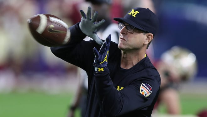 Michigan coach Jim Harbaugh warms up the quarterbacks before the Orange Bowl on Friday, Dec. 30, 2016 in Miami Gardens, Fla.