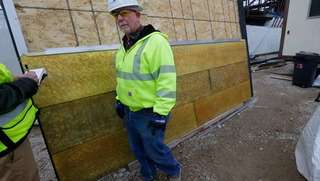 Denver Callahan, senior superintendent for Mortenson Construction, stands near samples of the bronze colored zinc panels that will cover the outer structure of the new Milwaukee Bucks arena.