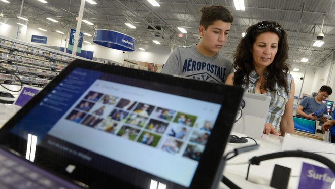 Rita Calderon and Joaquin Jimenez  browse in the computer section at a Best Buy in Falls Church, Va.