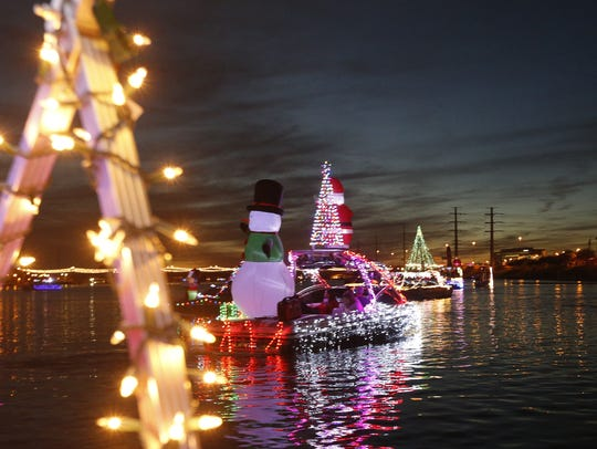 Boats dressed in lights and holiday decorations make