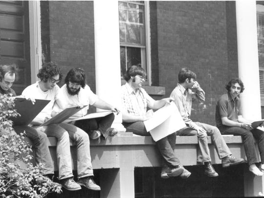 St. Michael's students in an art class in the 1970s sit on the porch of Sloane Hall with sketch books.