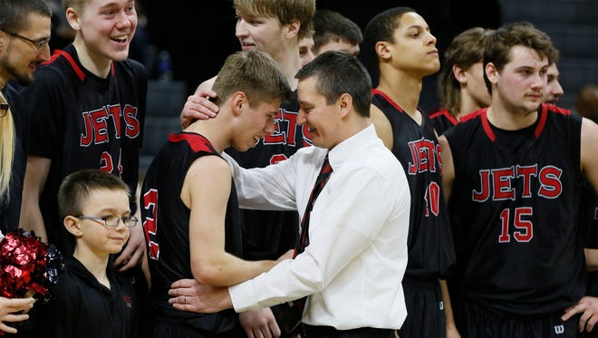 Powers North Central's Ryan Whitens gets a hug from head coach Adam Mercier as they wait through the postgame ceremony after their 67-47 win over Morenci in the MHSAA Class D boys basketball final March 28, 2015, at Breslin Center.