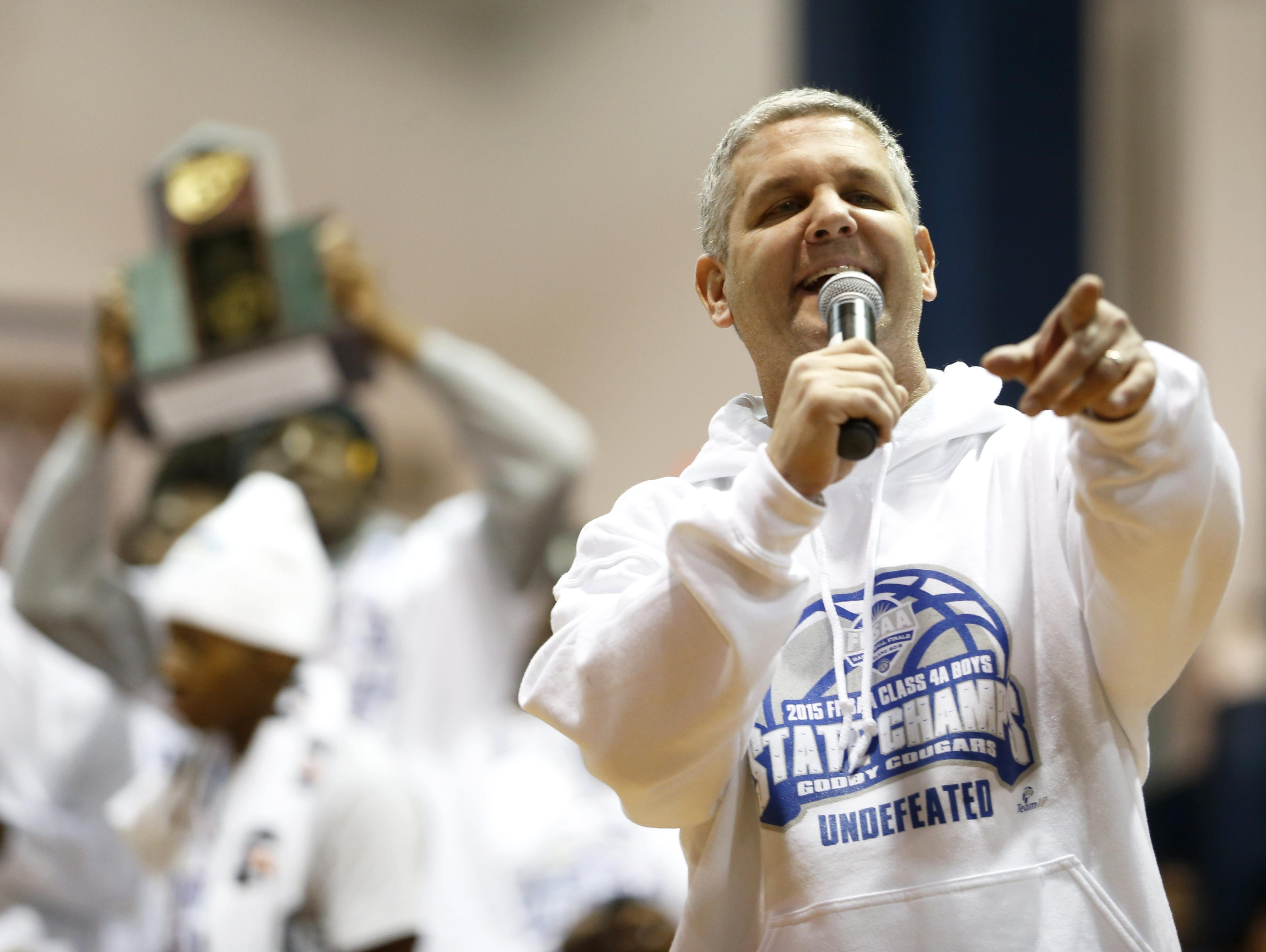 Godby coach Andy Colville speaks to the crowd of celebrators after the Cougars won a state title last season by going 31-0.