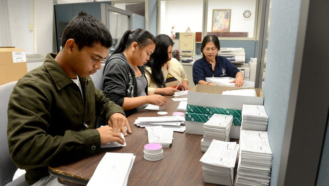In this 2013 file photo, Department of Administration staff place income tax refund checks in envelopes.