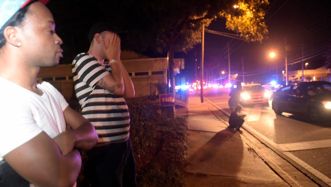 Jermaine Towns, left, and Brandon Shuford wait down the street from a shooting at Pulse, a nightclub in Orlando, Fla., Sunday, June 12, 2016. Towns said his brother was in the club at the time.