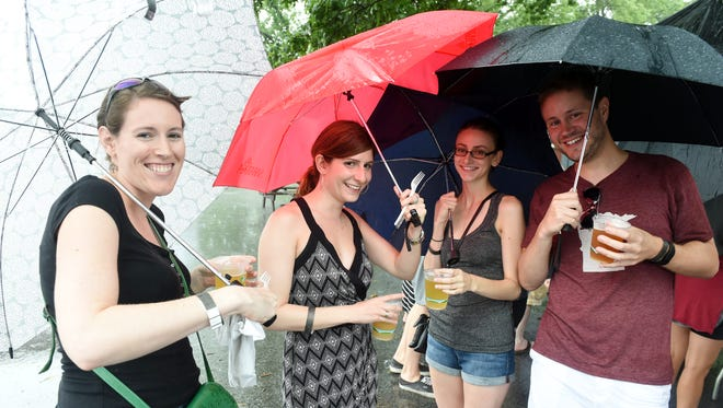 From left, Kiera Caponi, Anne Friedman, Colleen Meager and Ryan Rettmann were glad to have brought their umbrellas during Saturday's rain at the Firefly Feast in Beacon.