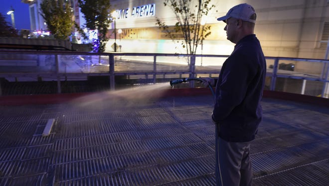 Leny Davis of Ice Cold Entertainment works to prepare an outdoor skating rink in Hall of Fame Park across the street from Bridgestone Arena on Monday, Nov. 14, 2016.