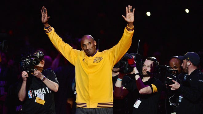 Los Angeles Lakers forward Kobe Bryant (24) waves to the crowd as he walks on the court before his final NBA game.