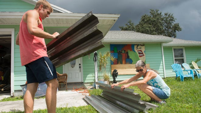 "Josh Steppling (left), of Jensen Beach, helps Debra Fischer, of Palm City, prepare her home for Hurricane Irma on Wednesday in Palm City. Steppling posted his phone number on Facebook, offering to help those in need board up their homes, but considered Fischer's house a priority. Steppling was joined by brother Danny Steppling and longtime friend Ian Weber, all of whom have known Fischer for many years through their friendship with her son Clay Fischer, who died in an April accident in Palm City. ""It's a beautiful, beautiful thing,"" Fischer said of their help."