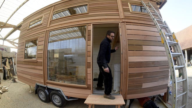 """A worker builds a """"Tiny House"""", a genuine wooden house on a trailer chassis."""