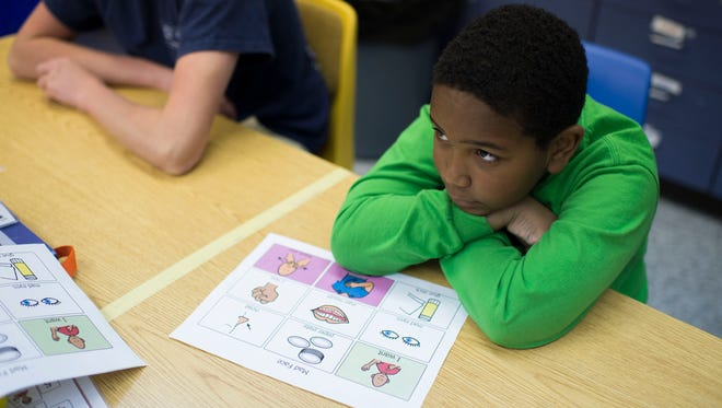 Rayshawn Brown listens as speech pathologist Wendy Ryan conducts a lesson Tuesday at Cedar Chapel Special School in Snow Hill.