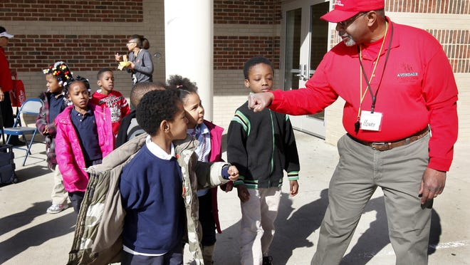 Henry Brown, founder of the Avondale Running Club, prepares students at Rockdale Academy for a run in 2012. Brown has organized Sunday's first Avondale 5-kilometer run.