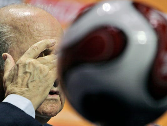FILE - In this  Sunday, Nov. 25, 2007 file photo FIFA President Sepp Blatter rubs his eye as he speaks at a press conference at the ICC in Durban, South Africa.  FIFA President Sepp Blatter said he will resign from soccer's governing body amid a widening corruption scandal and promised Tuesday June 2, 2015 to call for fresh elections to choose a successor. (AP Photo/Tsvangirayi Mukwazhi, File)