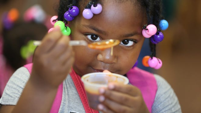 Corrionna Dudley, a first grader at Rees E. Price Academy in East Price Hill, tries some soup during a tasting in the fall. Suzy DeYoung, executive chef and owner of La Soupe, set up the tasting prior to delivering frozen soup to students each week. There are now 55 children signed up to receive the weekly soup delivery.