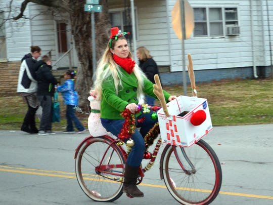The Uniontown Post Master, Carrie Griggs, participate in the parade on her festive bicycle.
