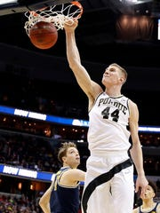 Purdue center Isaac Haas (44) dunks in front of Michigan forward Mark Donnal (34) during the second half of an NCAA college basketball game in the Big Ten tournament, Friday, March 10, 2017, in Washington. Michigan won 74-70 in overtime. (AP Photo/Alex Brandon)