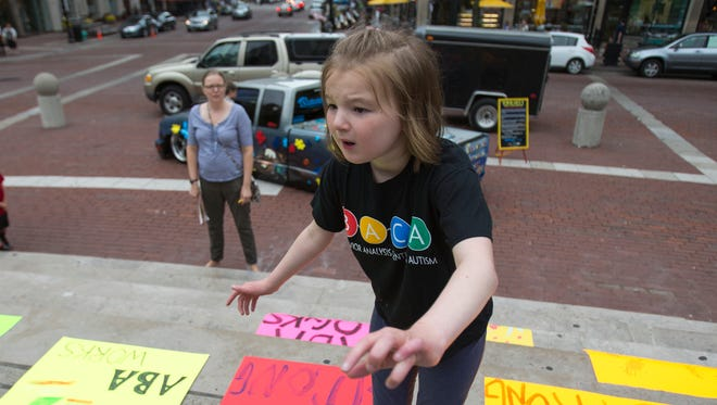 Ali DeMotte, 10, Indianapolis, who is autistic, is watched by her mother Jennifer DeMotte during a rally on Saturday, May 16, 2015, on Monument Circle to draw attention to Anthem Blue Cross and Blue Shield's coverage of children with autism and a lawsuit filed against the insurer. Parents of children with autism say the Indianapolis-based insurer should provide more coverage for therapies, such as applied behavior analysis. An Anthem spokesman said that it had paid thousands of claims last year for autism related services, including behavioral therapy.