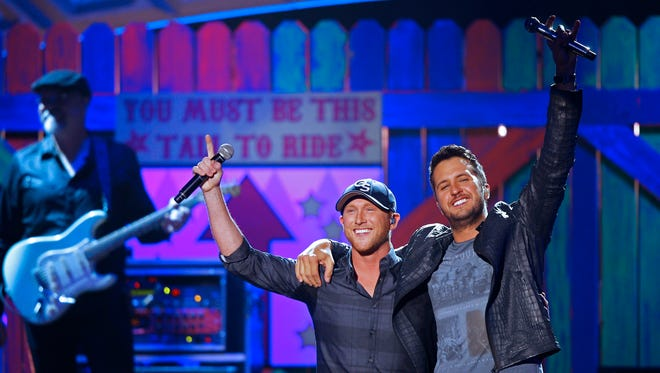 Luke Bryan, right, performs with Cole Swindell after winning Male Vocalist of the Year at the American Country Countdown Awards at the Music City Center on Monday, Dec. 15, 2014, in Nashville.