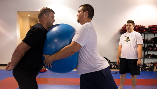 Scott Peters (left, former ASU and Cardinals offensive lineman) teaches proper blocking techniques to Marshal Nathe (center, Centennial High School), July 8, 2014, at the Fight Ready Fitness Center, 8666 E Shea Blvd., Scottsdale.