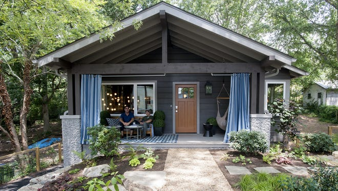 Designer Brian Patrick Flynn, left, and builder Jody Guokas, of JAG and Associates Construction, sit on the front porch of the HGTV Urban Oasis house in West Asheville in August.