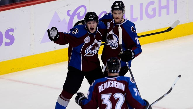 Colorado Avalanche center Matt Duchene (9) reacts to his second goal of the game against the Calgary Flames with center Mikhail Grigorenko (25) and defenseman Francois Beauchemin (32) in the third period at Pepsi Center. The Avalanche defeated the Flames 6-3.