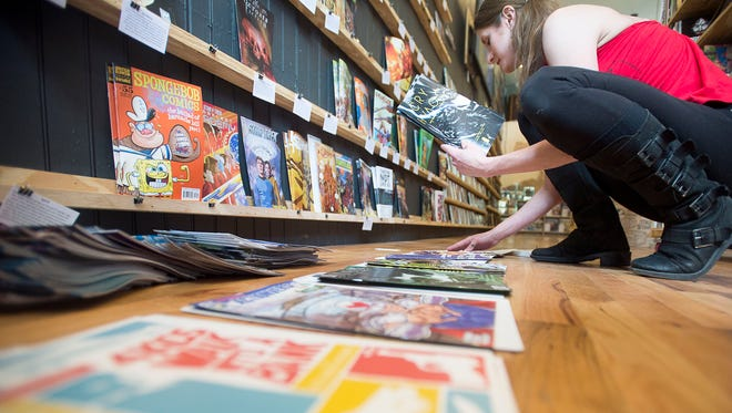 Sales assistant Morgan Albritton lays out new comics to be shelved April 27 at Haywood Comics in West Asheville. May 7 marks Free Comic Book Day across the country, and Haywood Comics will be giving away comics, gift cards, and more.