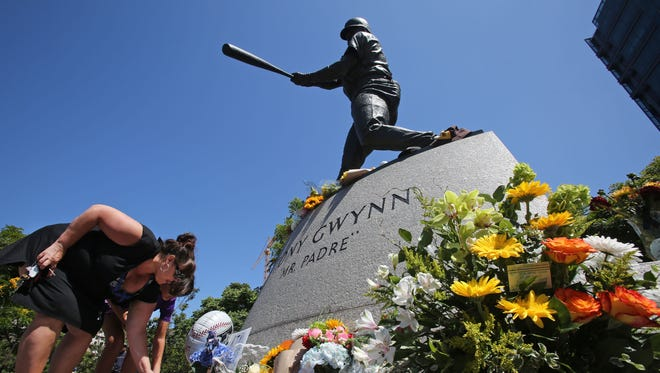 Fans place flowers at the base of a statue of the late San Diego Padres great Tony Gwynn at Petco Park, where the Padres play, June 16, 2014, in San Diego, California.