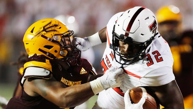 Texas Tech's Desmond Nisby carries the ball during the first half while defended by Arizona State's Joseph Bryant during the fort half of an NCAA college football game Saturday, Sept. 16, 2017, in Lubbock, Texas.