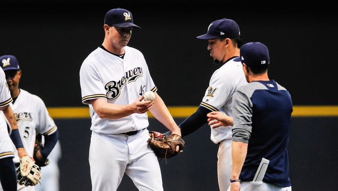 Brewers relief pitcher Corey Knebel hands the ball to manager Craig Counsell during the ninth inning Thursday against the Padres.