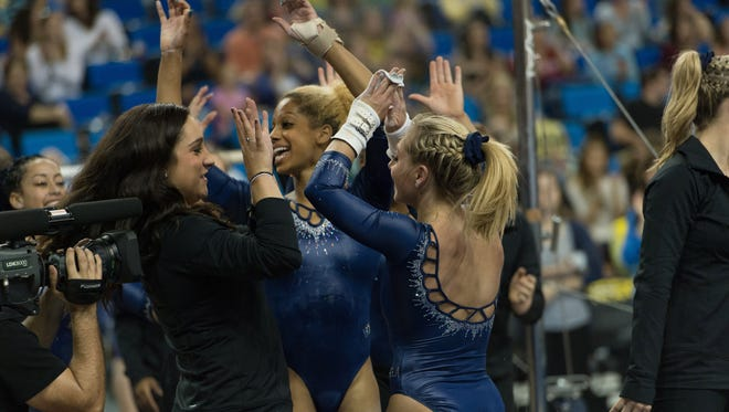 Team manager Jordyn Wieber, left, high fives the UCLA gymnasts during their meet against the Arizona Wildcats on Jan. 19 in Los Angeles.
