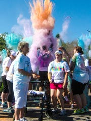 Clouds of dyed cornstarch stretch throughout the air at the end of Battle Creek's Color Out Cancer run.