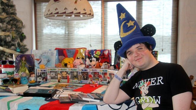 "Damian Kelly-Bateman poses with his large assortment of Disney memorabilia. ""I try to get them on sale,"" he said. ""The bags, I have a problem with."""