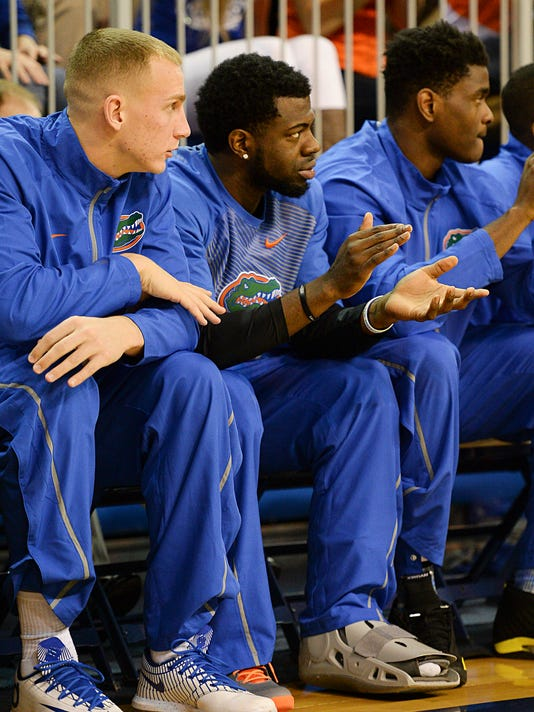 Florida guard Eli Carter, center, sits on the Florida bench next to Alex Murphy, left, with his foot in a cast during an NCAA college basketball game against Louisiana-Monroe in Gainesville, Fla., Friday, Nov. 21, 2014. (AP Photo/Phil Sandlin)