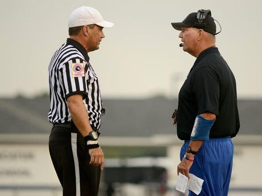 Referee Bob Cannon talks to Stephen Decatur head coach Bob Knox during the first quarter of a 2015 Friday night game at Stephen Decatur high.