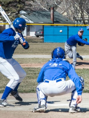 KCC pitcher Kyle Mallwitz throws the heat to Alex Holley as Alex Goodwin catches during a recent practice.