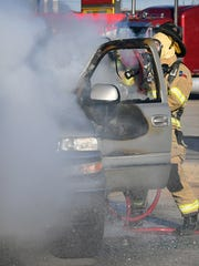 A Wichita Falls firefighter battles a vehicle fire
