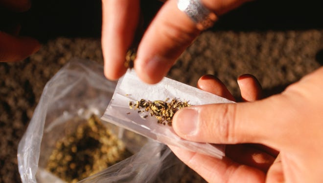 Person rolling joint, close-up of hands and bag of marijuana