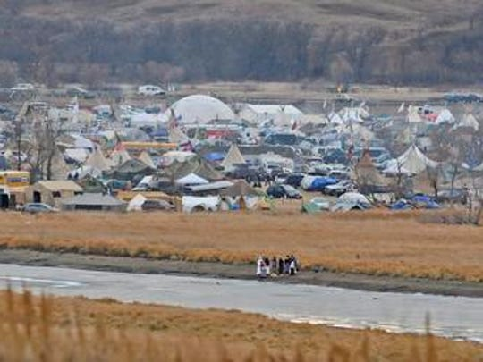 In this Nov. 24, 2016 photo, people stand on the edge of Cantapeta Creek near the growing Sacred Stones Overflow Protest Camp in Morton County, N.D. The leader of the Cheyenne River Sioux in South Dakota is calling for all opponents of the Dakota Access oil pipeline to boycott businesses in North Dakota's capital city.
