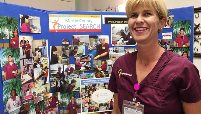 Andrea von Stralendorff, Project SEARCH teacher, stands with photos of program interns.