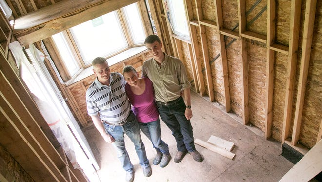 Edmund Coleman stands between his father and mother, Gary and Mary, inside an unfinished tiny home. Edmond will be attending West Point and will work on finishing the house with his father during school breaks.