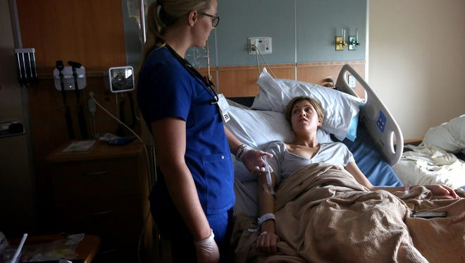 Breast cancer patient Jill Brzezinski-Conley receives treatment in 2014 for pain from nurse Chelsea Davis, left, at Norton Suburban Hospital in Louisville.  Sep. 11, 2014.