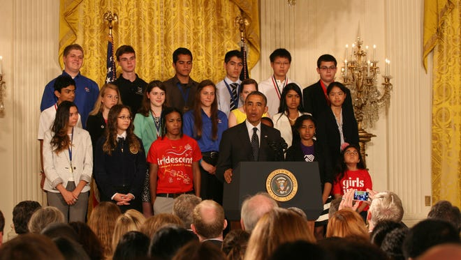 Phoenix teens Diserae Sanders - front row, left - and Martin Carranz and Quenan Ruiz - back row, center - listen as President Barack Obama announces new science education initiatives during the White House Science Fair.