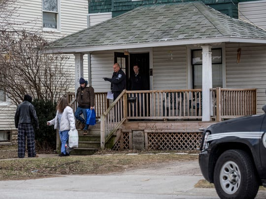 People are removed from the home as police prepare to lock and board it Friday, Jan. 6, 2016 at 2010 Farrand Street in Port Huron. The home was locked and boarded as part of an effort to stop illegal activities at the home and in the neighborhood.